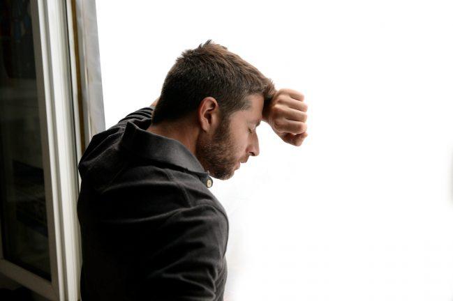 Mann verzweifelt an Fenster